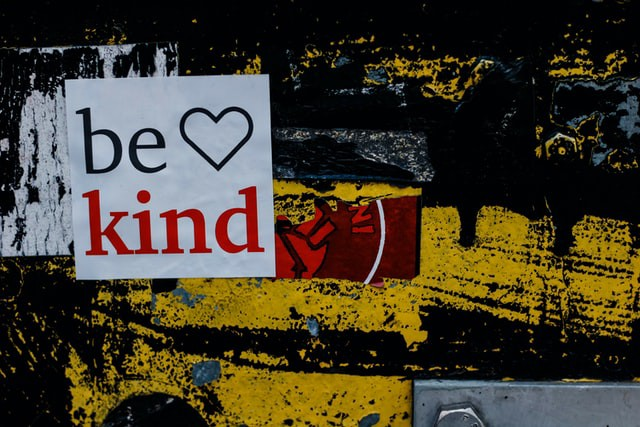 """""""Be Kind"""" sign on wall with black and yellow graffiti"""