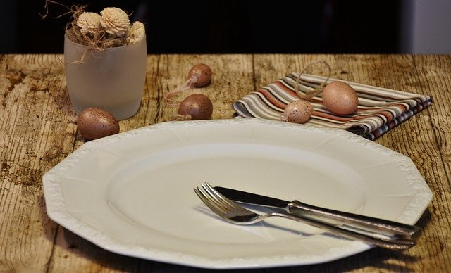 an empty plate, fork, knife, napkin, and vase sit on a wooden table
