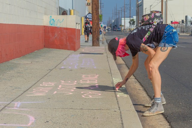 Girl with pink hair and tattoos writes with chalk on sidewalk.
