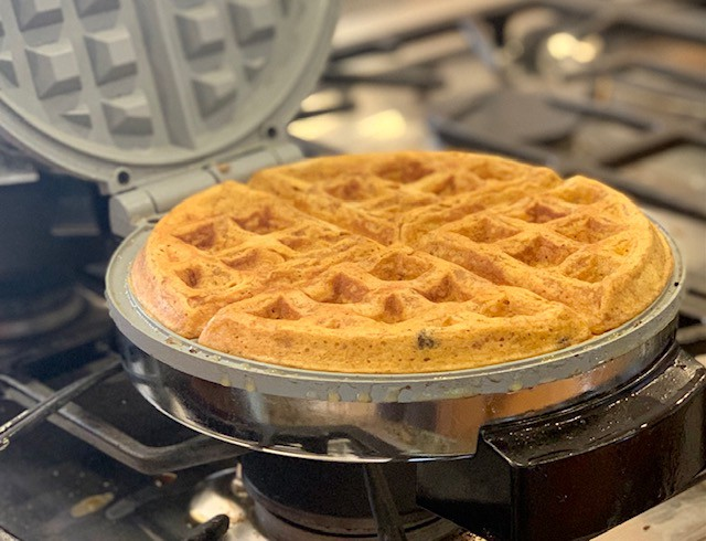 Pumpkin and chocolate chip waffles in waffle-maker.