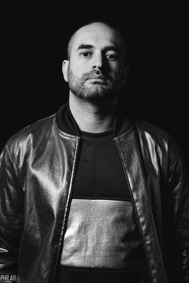 Black and white photograph of David Ordonez DJ, producer and new NFT Art Gallery founder and creator. David has a bald head, stubble and is wearing a black leather jacket.