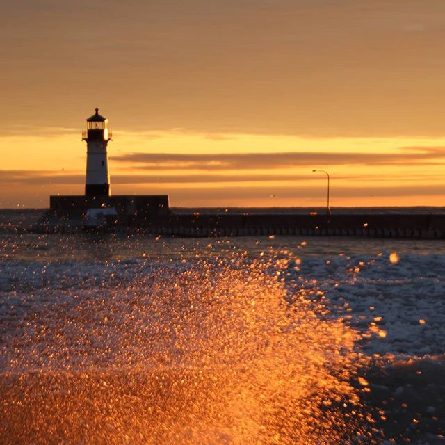 Spray with the lighthouse as a backdrop