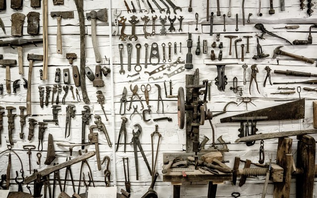 Wooden wall with lots of different old tools hanging from it.