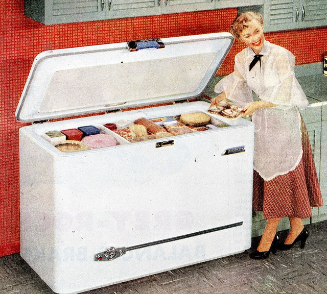 A color advertisement from the 1950's shows a smiling woman showing off a chest freezer stocked with food