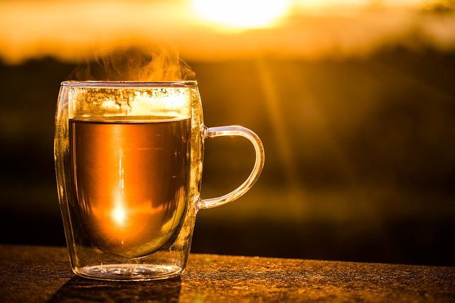 glass cup with hot tea, steam rising from the top. cup is sitting on a ledge with the background showing the bright sun. How Tea Became the Most Consumed Beverage in the World by Nancy Blackman. tea. herbs. herbal medicine. tea drinking