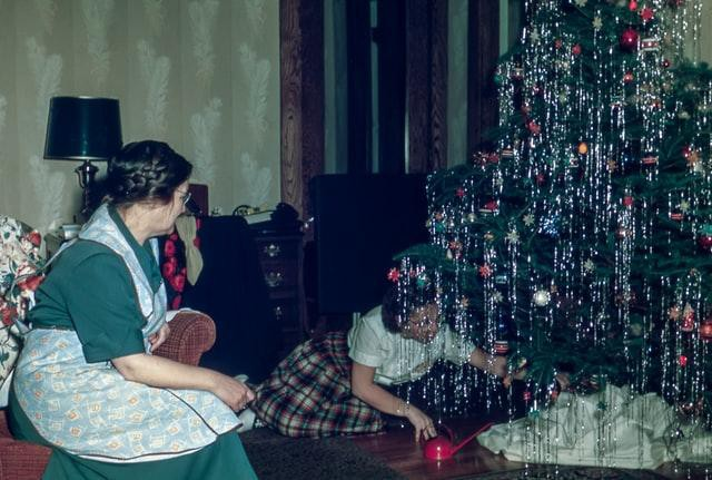 A mother watches her child decorate a Christmas tree.