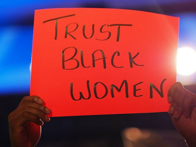 A bright red poster with the phrase: Trust Black Women