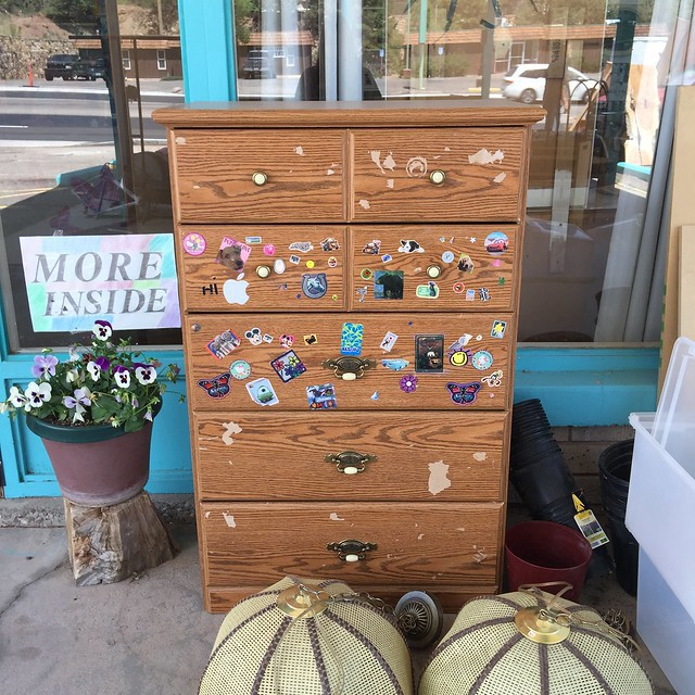 An otherwise ordinary dresser tricked out with random stickers at Hey Mavis! thrift shop in Cedar Crest, New Mexico