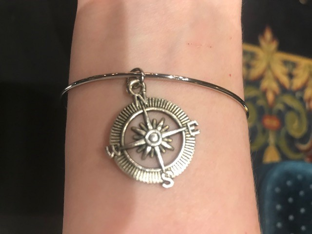A silver bracelet with a compass charm.