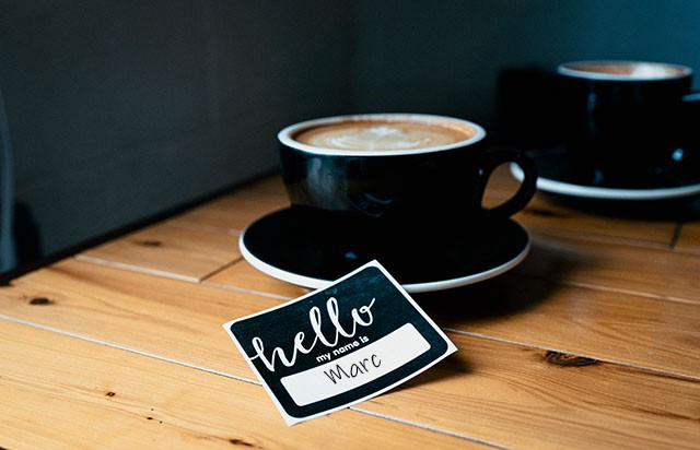 Coffee Cup and Name Tag on Table