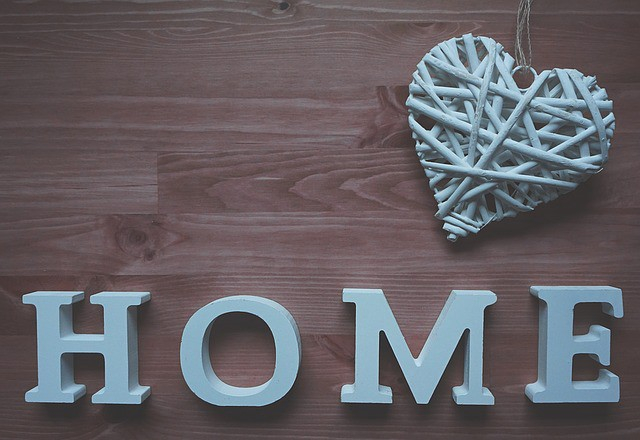 Woven heart decoration and a home sign next to each other on a wood desk