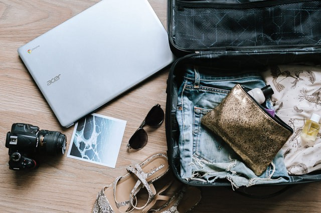 Open suitcase, half packed with camera, laptops, sunglass lay next to it.