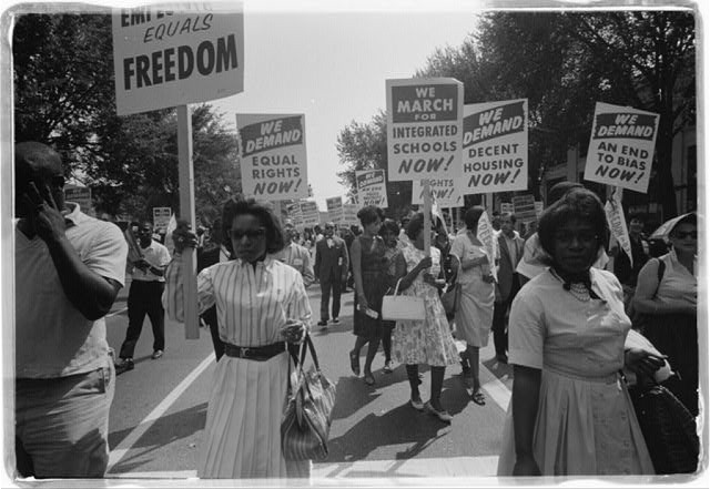 A photo of Black women marching with signs for equal rights, integrated schools, decent housing, and an end to bias.