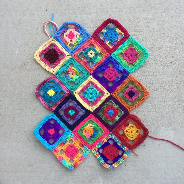 Seventeen four-inch flamboyant granny squares ready to become a purse