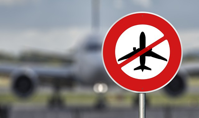 Sign showing a aeroplane crossed out with an out-of-focus plane in the background.