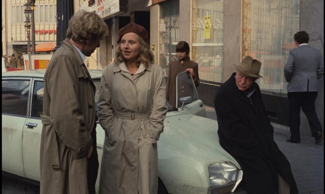 A man and a woman stand talking while an old man sits on the hood of a car and observes.