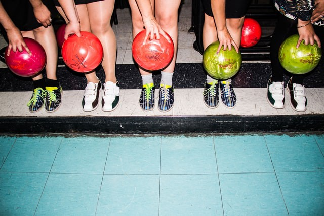 Five people in row holding different bowling balls. (pic from https://unsplash.com/@danielalvasd)