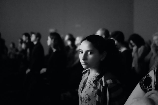Black and white photo with a young girl in focus glancing toward the camera. Her face is absent of emotion. No smile, no frown either. The room is crowded with people. She looks alone and maybe afraid.