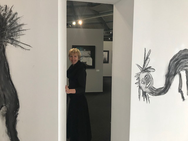Margot in a doorway between to child-like nightmarish drawings