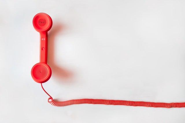 Red corded telephone on white surface.