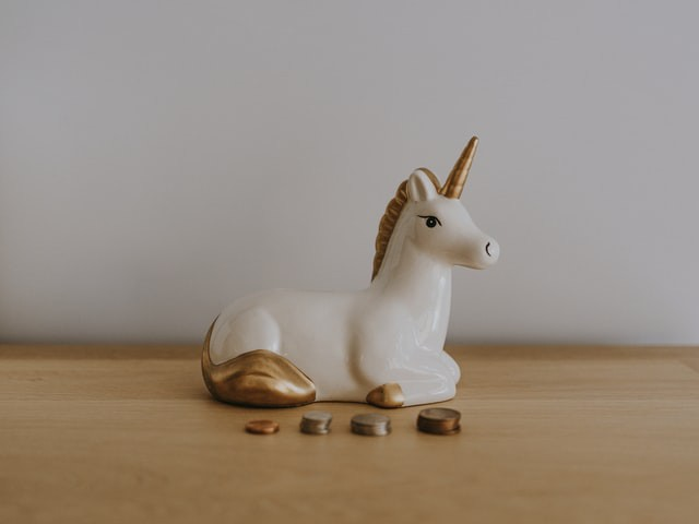 Ceramic white unicorn with a gold horn sitting in front of stacks of coins.