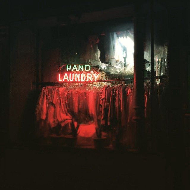 "a neon ""hand laundry"" sign glows in the window of a laundry above a rack of hanging shirts wrapped in plastic"