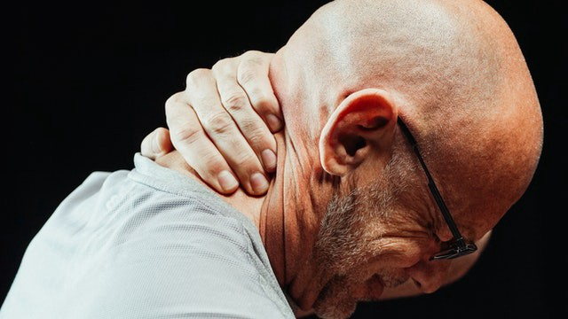 A side profile of a bald man in glasses gripping the back of his neck, while eyes are closed and wincing in pain.