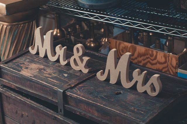 Cursive wood blocks painted brown read Mr./Mister and Mrs./Missus and sit on a brown wooden trunk in front of wire shelves that are full.