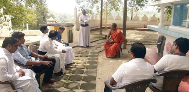White-robed Christian monks and orange-robed Hindu monk sit in a circle during inter-faith dialogue at a Sri Lanka monastery.