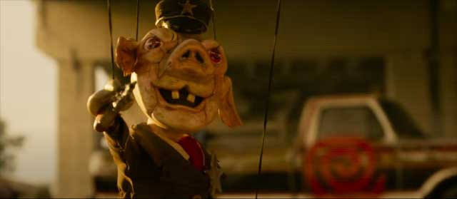 A creepy looking antique puppet with a pig's face holding a tiny toy gun