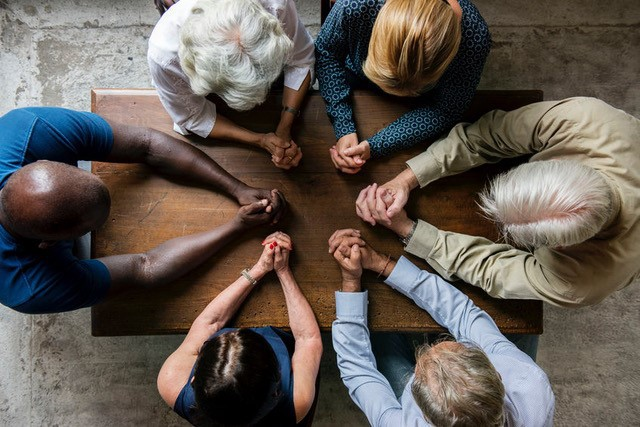 Multi-racial group with hands clasped in prayer seated around a square wooden table.