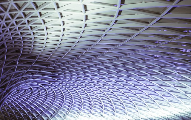 The complex roof structure of Kings Cross train station in London showing an intricate pattern of triangular steel beams.