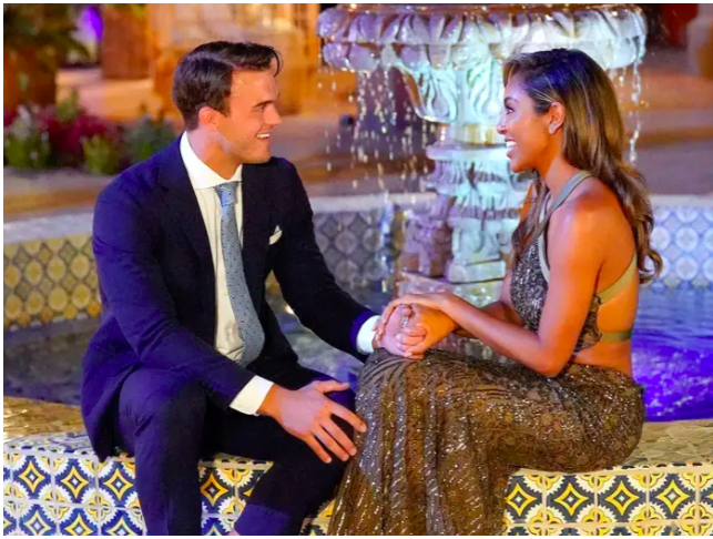 A man, Ben Smith, holds hands and smiles at a woman, Tayshia Adams, in front of a fountain at La Quinta Resort.