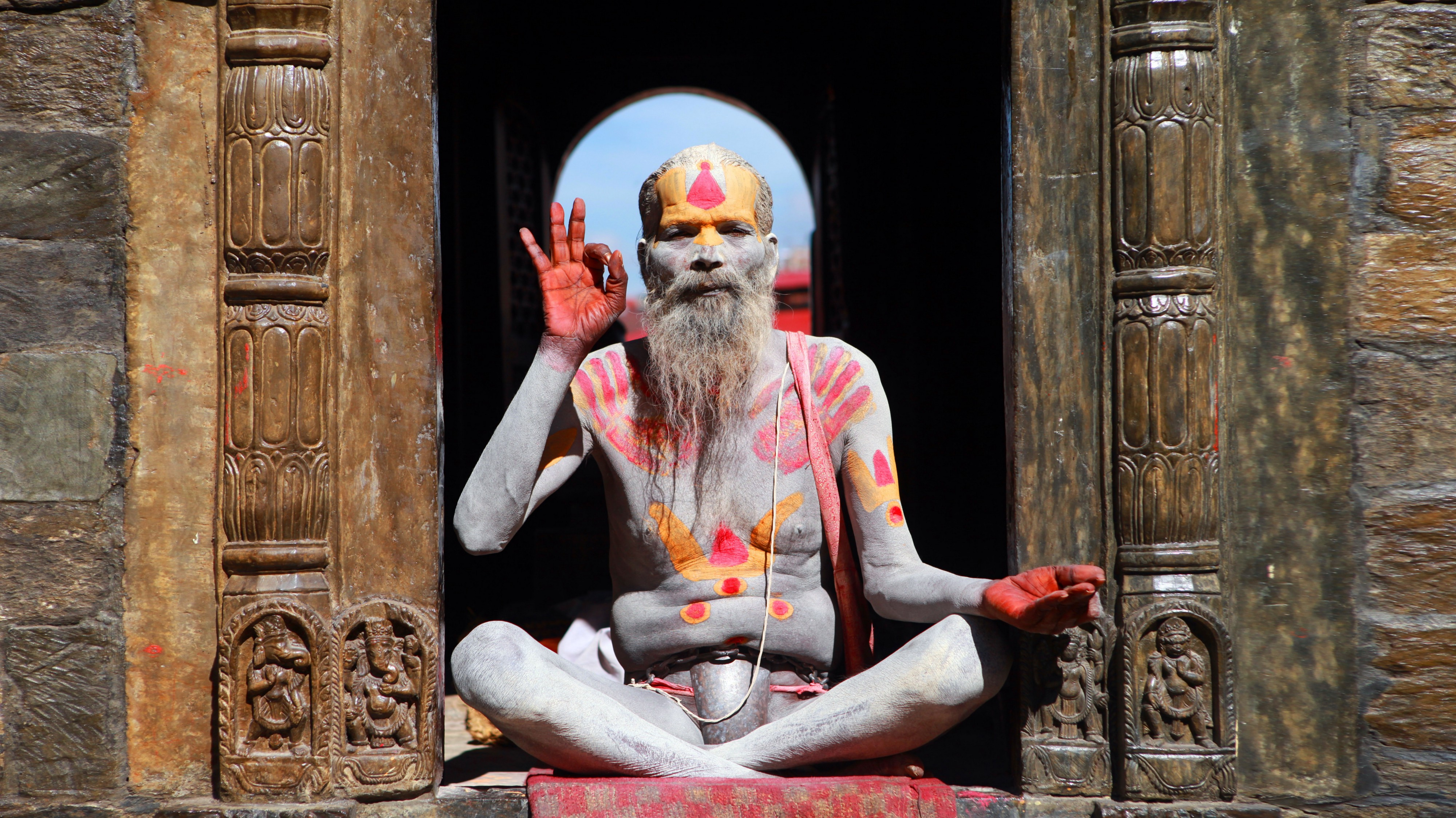 Indian meditation guru sitting cross-legged and covered in body paint