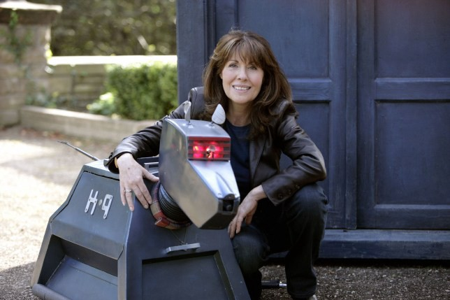 Elisabeth Sladen as Sarah Jane Smith, posing with K9 in front of the TARDIS.