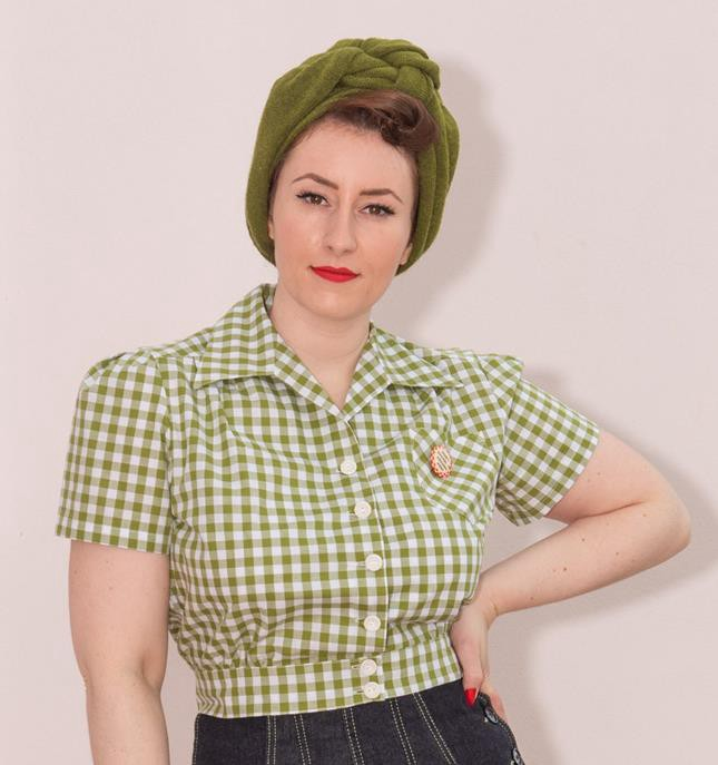 A woman wearing a midcentury-style green turban and a green gingham 1940s-style work blouse.
