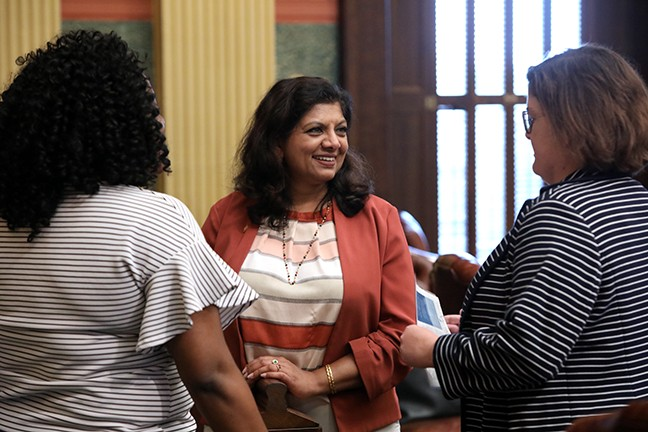 Padma kuppa smiles and talks to colleagues on the michigan house floor
