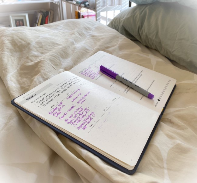 SELF journal on a bed with handwritten notes