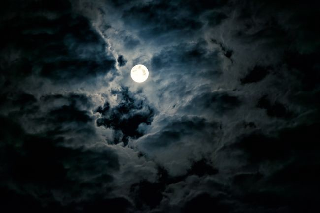 The full moon visible through clouds in the night sky