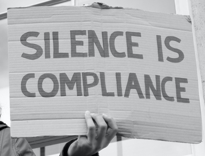 https://commons.wikimedia.org/wiki/File:Silence_is_compliance_-_A_protester_with_a_message_standing_on_a_window_ledge_in_Whit