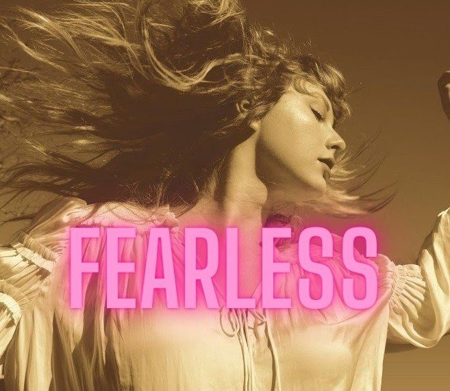 """Taylor Swift is wearing a white address with her hair flying in the wind looking sideways and the lettering """"fearless."""""""