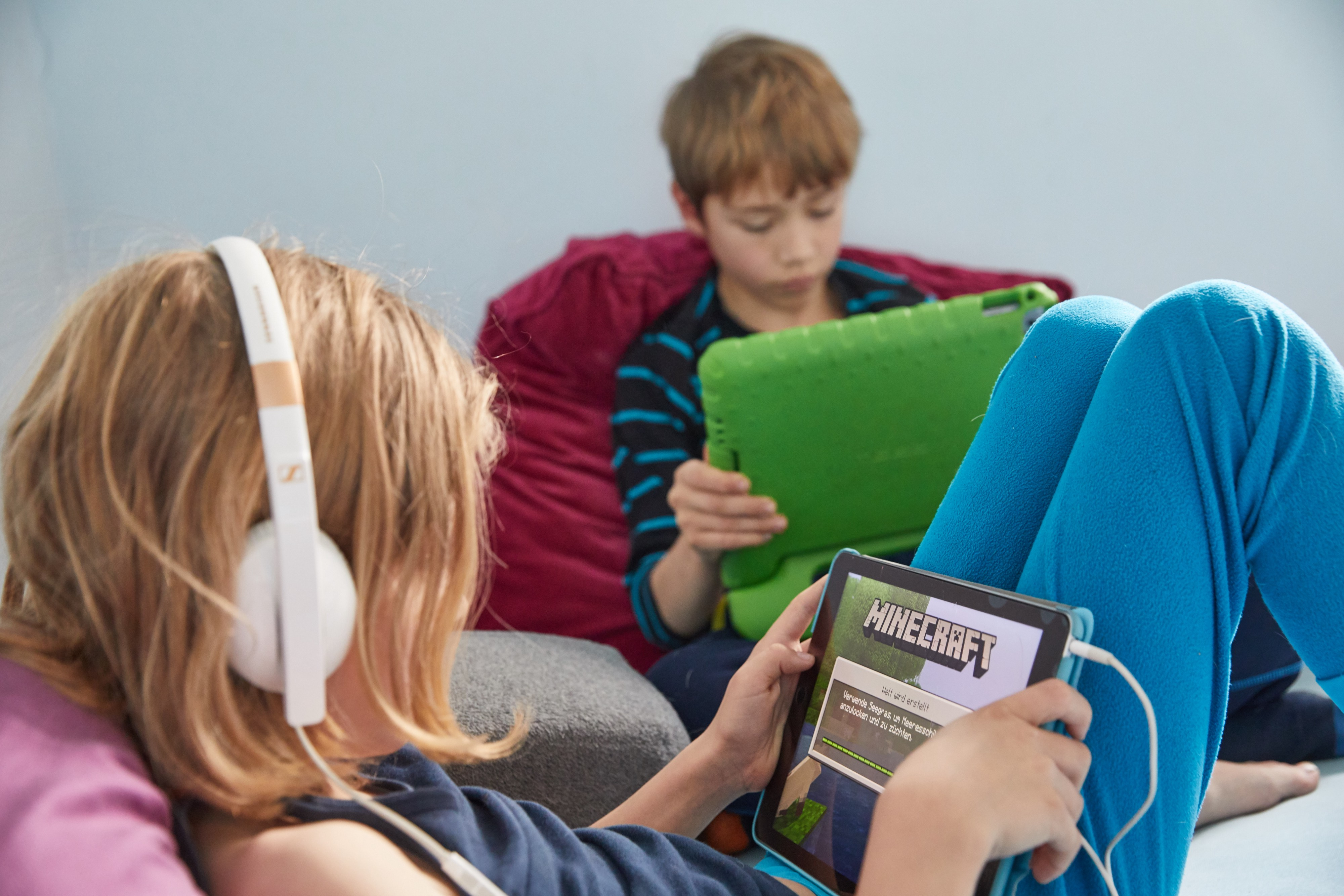 Two young children play the open world game Minecraft on their iPads.