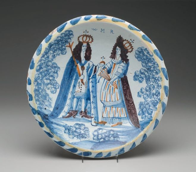 Blue and white ceramic plate featuring a portrait of a king and queen.