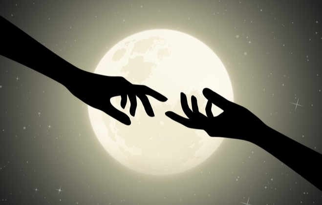 Two hands silhouetted by the moon