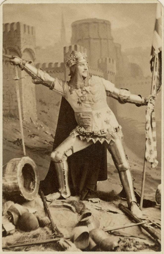 An actor posing dramatically, sword in one hand, flag in the other, wearing a theatrical version of medieval royal garb.
