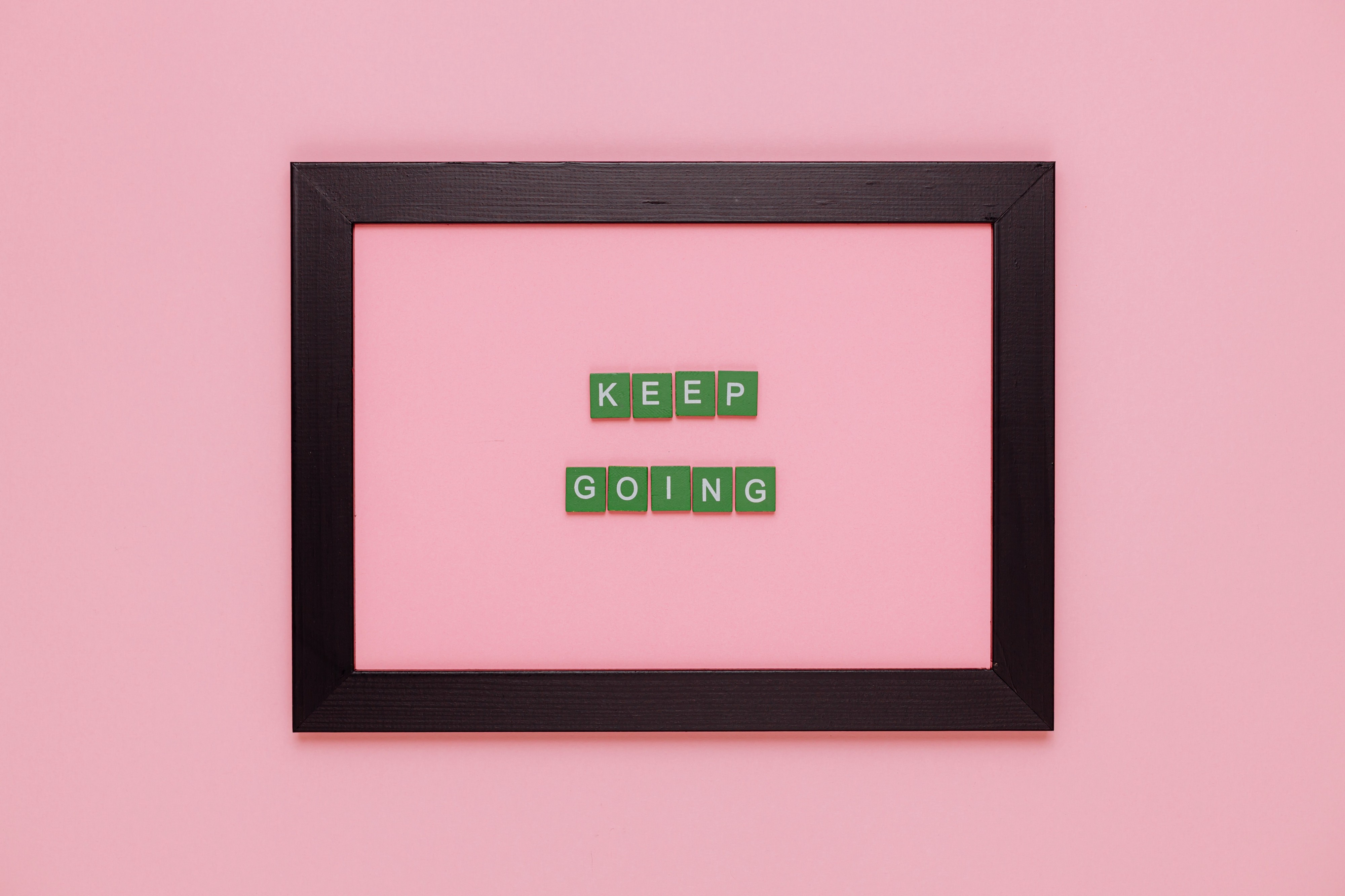 """Pink frame that says """"KEEP GOING"""" in small green block letters."""
