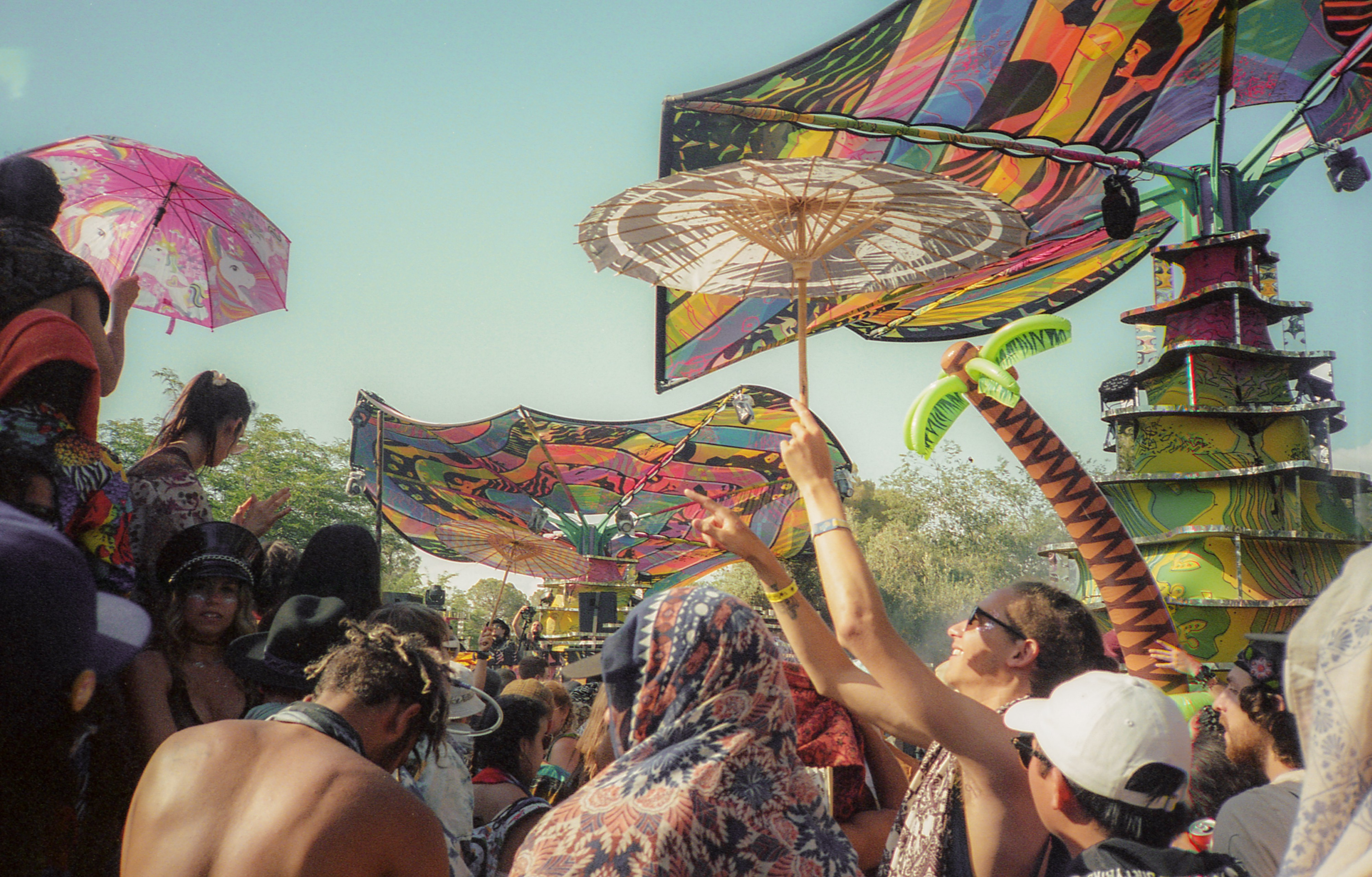 A colorful shot of a crowd dancing at a music festival