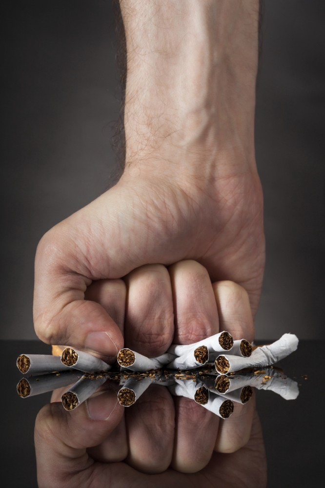 A man crushing cigarettes in determination to quit smoking
