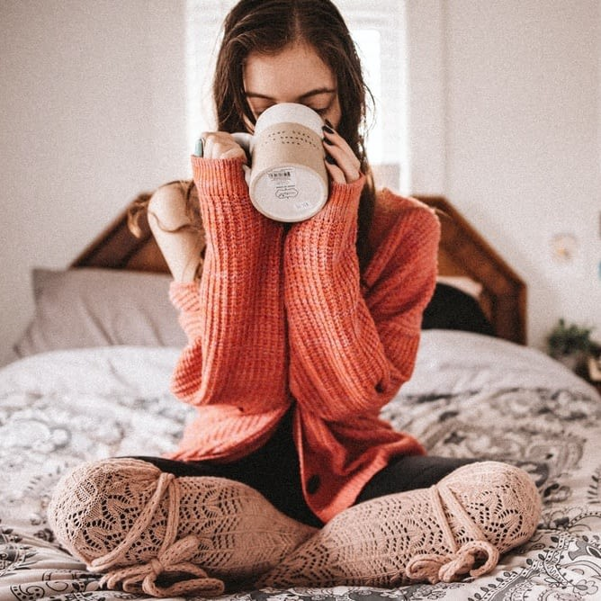 Woman in red knit sweater sitting on bed sipping out of a mug