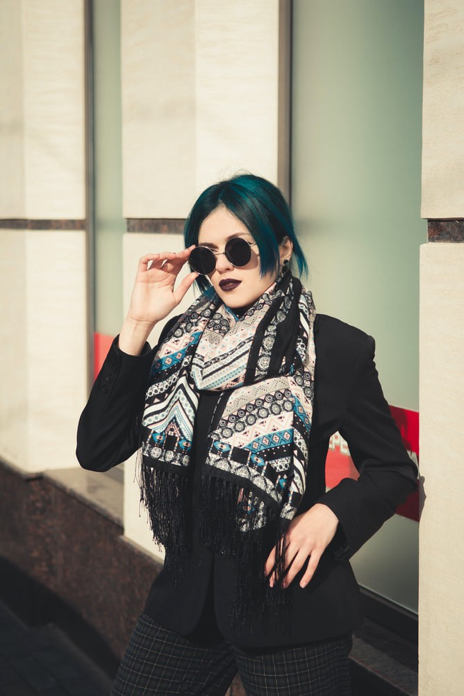 A green-haired woman wearing a fashionable neck scarf and sunglasses